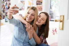 Dos adolescentes que toman Selfie en dormitorio en casa Foto de archivo