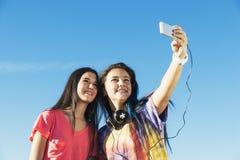 Dos adolescentes que toman Selfie en parque Imagen de archivo libre de regalías