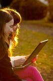 Dos adolescentes que trabajan en el cuaderno en el parque Imagen de archivo