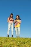 Dos adolescentes que usan el móvil en parque Imagenes de archivo