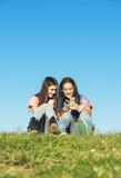 Dos adolescentes que usan el móvil en parque Imagen de archivo