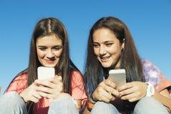 Dos adolescentes que usan el móvil en parque Fotos de archivo libres de regalías
