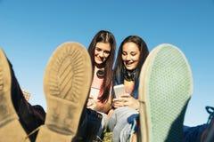 Dos adolescentes que usan el móvil en parque Fotos de archivo
