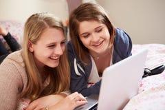 Dos adolescentes que usan el ordenador portátil en dormitorio Foto de archivo libre de regalías