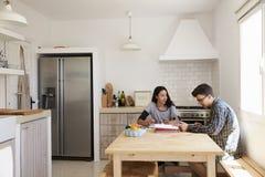 Dos adolescentes que usan el ordenador portátil estudian juntos en la tabla de cocina Foto de archivo