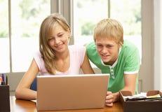 Dos adolescentes que usan la computadora portátil en el país Foto de archivo libre de regalías
