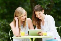 Dos adolescentes que usan la tableta de Digitaces en café al aire libre Fotografía de archivo