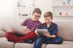 Dos adolescentes que usan la tableta en el sofá en casa Foto de archivo