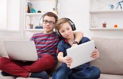Dos adolescentes que usan la tableta en el sofá en casa Foto de archivo libre de regalías