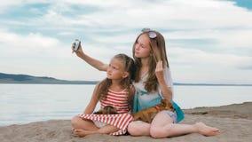 Dos adolescentes se están sentando en una playa arenosa, en Internet en teléfono Imagenes de archivo
