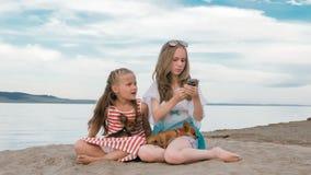 Dos adolescentes se están sentando en una playa arenosa, en Internet en teléfono Fotografía de archivo