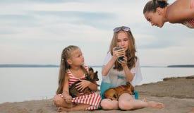 Dos adolescentes se están sentando en una playa arenosa, en Internet en teléfono foto de archivo libre de regalías