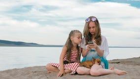 Dos adolescentes se están sentando en una playa arenosa, en Internet en teléfono fotos de archivo libres de regalías