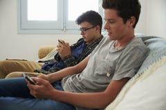 Dos adolescentes se relajan, los amigos de la mensajería con smartphones Fotografía de archivo libre de regalías