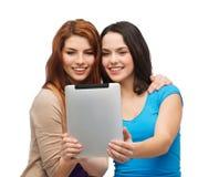 Dos adolescentes sonrientes con el ordenador de la PC de la tableta Fotografía de archivo
