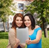 Dos adolescentes sonrientes con el ordenador de la PC de la tableta Imágenes de archivo libres de regalías
