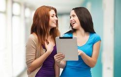 Dos adolescentes sonrientes con el ordenador de la PC de la tableta Imagenes de archivo