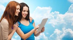 Dos adolescentes sonrientes con el ordenador de la PC de la tableta Imagen de archivo