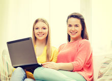 Dos adolescentes sonrientes con el ordenador portátil en casa Fotos de archivo libres de regalías