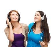 Dos adolescentes sonrientes con los auriculares Imágenes de archivo libres de regalías