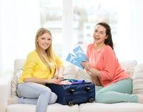 Dos adolescentes sonrientes con los billetes de avión Imagen de archivo libre de regalías