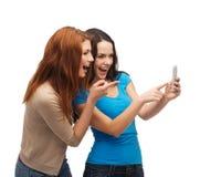 Dos adolescentes sonrientes con smartphone Fotos de archivo libres de regalías
