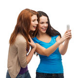 Dos adolescentes sonrientes con smartphone Fotografía de archivo libre de regalías