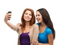 Dos adolescentes sonrientes con smartphone Fotos de archivo