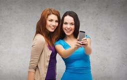Dos adolescentes sonrientes con smartphone Foto de archivo