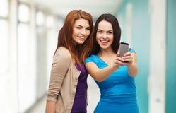 Dos adolescentes sonrientes con smartphone Imagen de archivo libre de regalías