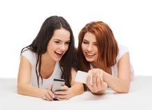 Dos adolescentes sonrientes con smartphones Imagen de archivo libre de regalías