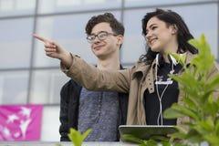 Dos adolescentes sonrientes, donde hay un lugar en ciudad que necesitan Fotografía de archivo libre de regalías