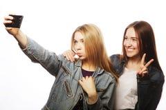 Dos adolescentes sonrientes que toman la imagen con la cámara del smartphone Fotografía de archivo