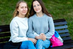 Dos adolescentes Verano en un banco en ciudad después de la escuela Reclinación feliz deteniéndose manos del ` s El concepto es e Fotos de archivo libres de regalías