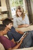 Dos adolescentes y madre que se sientan en el ordenador de Sofa At Home Using Tablet imagenes de archivo