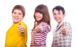 Dos adolescentes y una muchacha que muestran los pulgares para arriba Fotos de archivo libres de regalías
