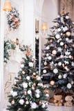 Dos adornaron el árbol de navidad, la guirnalda y la chimenea clásica Imagenes de archivo