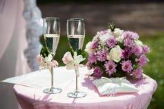 Dos adornaron las copas con champán, las almohadas del anillo y weddi Foto de archivo libre de regalías
