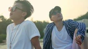 Dos adultos asiáticos jovenes que se relajan al aire libre almacen de metraje de vídeo