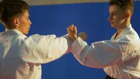 Dos adultos jovenes que llevan el kimono que hace el entrenamiento del karate y que practica bloqueando técnicas almacen de video