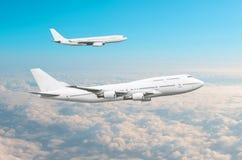 Dos aeroplanos blancos grandes del pasajero vuelan paralelo en el cielo sobre las nubes Imagen de archivo libre de regalías