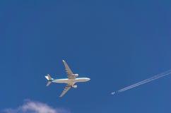 Dos aeroplanos en las trayectorias de la travesía del cielo en diverso trav del vuelo Imagen de archivo libre de regalías