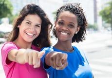 Dos africanos y mujeres caucásicas que señalan en la cámara en la ciudad Imagenes de archivo