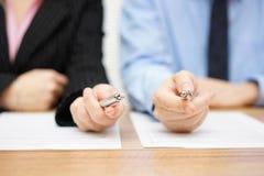 Dos agentes que dan a su cliente una pluma para firmar un trato foto de archivo