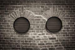Dos agujeros redondos en pared de ladrillo foto de archivo