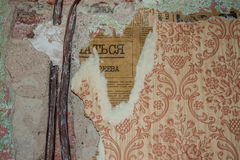 Dos alambres viejos que se pegan fuera del yeso y del papel pintado rugoso con un pedazo de periódico viejo Fotografía de archivo