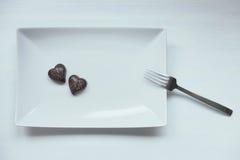 Dos almendras garapiñadas en forma de corazón del chocolate en una placa blanca Imágenes de archivo libres de regalías