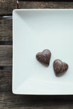 Dos almendras garapiñadas en forma de corazón del chocolate en una placa blanca y de madera Fotografía de archivo libre de regalías