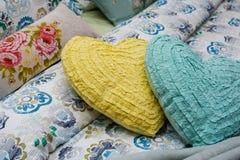 Dos almohadas bajo la forma de mentira de los corazones en la cama Fotografía de archivo libre de regalías