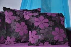 Dos almohadas púrpuras con las flores en el fondo azul blanco Foto de archivo libre de regalías